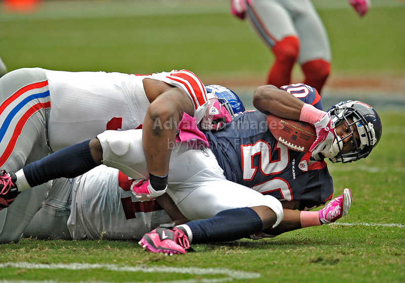 10 Oct 2010:  <br /> Houston Texans running back Steve Slaton #20 is pulled down from behind by New York Giants defensive end Justin Tuck #91<br /> in a game between the New York Giants and the Houston Texans at Reliant Stadium in Houston Texas.<br /> Giants win 34-10