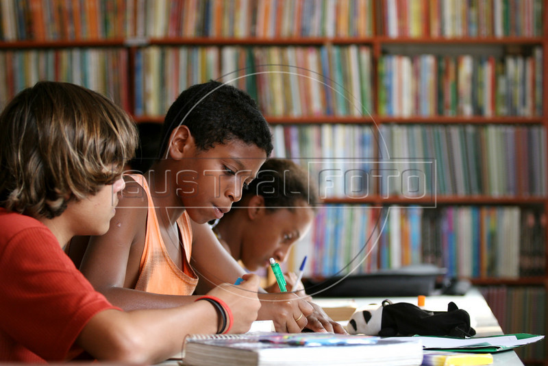 Students study during the afternoon at the community library in the Jardin Catarina neighborhood of Sao Goncalo, a poor city in the metropolitan Rio de Janeiro area, Sept. 19, 2005. Hoping to give neighborhood children a better education than they received, Carlos Luiz Leite and his wife Maria de Penha de Oliveira Mello started the library in their home in 2003 with about 100 books using their own money and labor. It has grown to over 5000 titles and their tiny home is filling with books as donations arrive, including brand new items from book publishers. Adults also use the resources to study, many who quit school early to work. (Australfoto/Douglas Engle)