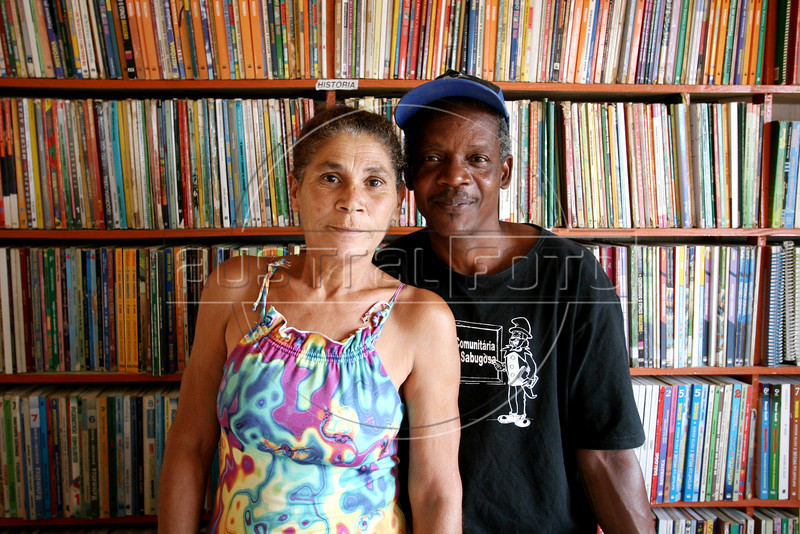 Carlos Luiz Leite and  Maria de Penha de Oliveira Mello in their home-turned-library in the Jardin Catarina neighborhood of Sao Goncalo, a poor city in the metropolitan Rio de Janeiro area, Sept. 19, 2005. Hoping to give neighborhood children a better education than they received, the couple a library in their home in 2003 with about 100 books using their own money and labor. It has grown to over 5000 titles and their tiny home is filling with books as donations arrive, including brand new items from book publishers. Adults also use the resources to study, many who quit school early to work. (Australfoto/Douglas Engle)