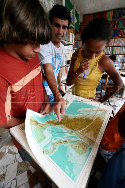 Volunteer Helio Sampaio, center, helps students study geography at the community library in the Jardin Catarina neighborhood of Sao Goncalo, a poor city in the metropolitan Rio de Janeiro area, Sept. 19, 2005. Hoping to give neighborhood children a better education than they received, Carlos Luiz Leite and his wife Maria de Penha de Oliveira Mello started the library in their home in 2003 with about 100 books using their own money and labor. It has grown to over 5000 titles and their tiny home is filling with books as donations arrive, including brand new items from book publishers. Adults also use the resources to study, many who quit school early to work. (Australfoto/Douglas Engle)