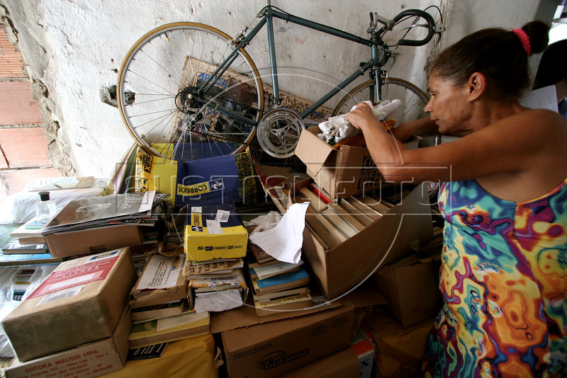 Maria de Penha de Oliveira Mello looks through books which have piled up in her home in the Jardin Catarina neighborhood of Sao Goncalo, a poor city in the metropolitan Rio de Janeiro area, Sept. 19, 2005. Hoping to give neighborhood children a better education than they received, Maria de Penha de Oliveira Mello and husband Carlos Luiz Leite started a community library in their home in 2003 with about 100 books using their own money and labor. It has grown to over 5000 titles and their tiny home is filling with books as donations arrive, including brand new items from book publishers. Adults also use the resources to study, many who quit school early to work. (Australfoto/Douglas Engle)