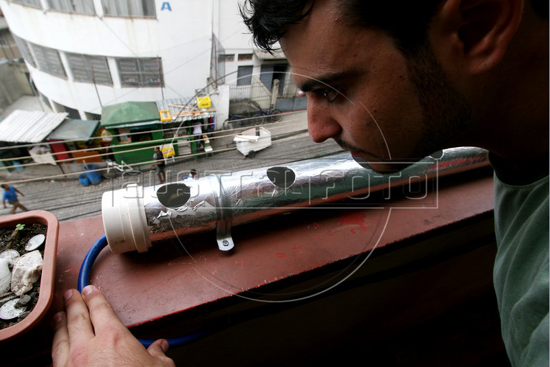 Group leader Josh Meyer inspects a water hose used on a hydroponic growing device in the Santa Marta slum in Rio de Janeirio, August 19, 2005. Using hydroponics, a little hard labor and lots of ingenuity, the Temple University students spend their vacation time building and installing a farming apparatus that turns the walls and roofs of slum residents into small gardens. The technology, part of a broader environmental movement known as green roofing, helps residents compensate for land shortages by supporting miniature plant nurseries from their homes. Green roofing is popular in Europe for its environmental and aesthetic benefits, but this is an initial attempt to show that the technology can also provide sustenance for the poor. (Australfoto/Douglas Engle)(Australfoto/Douglas Engle)(Australfoto/Douglas Engle)