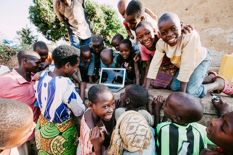 kids crowding around laptop in Rwanda