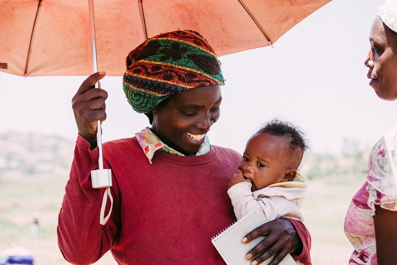 woman holding umbrella and baby in Rwanda