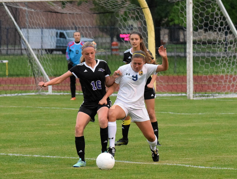 Woodhaven's Jackie Berceau (left) and Trenton's Marla Cobetto battle for the ball on Wednesday night during the Downriver League finale. The host Trojans defeated the Warriors 3-1 and claimed the outright league championship. (MIPrepZone Photo Gallery by Frank Wladyslawski)