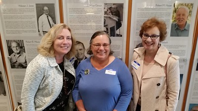 Katrin Hecht, Mary Andrews and Mary Allen pose in front of Hall of Fame teachers, Web Jones, Bob Wentz, Fabian Giroux and Don Ulander