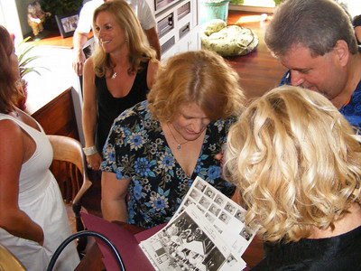 Classmates view old school photos at Leslie Feducia Louvier's party