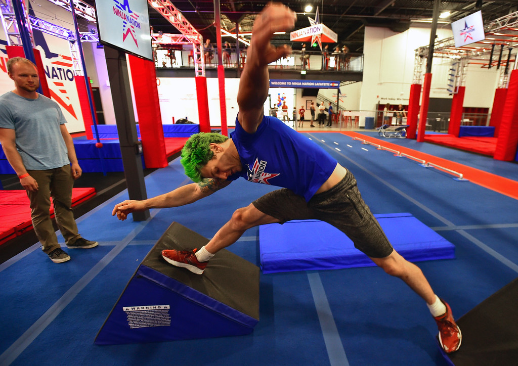 . Instructor Jamie Rahn demonstrates the improper way move from one obstacle to another in the Quad Jump area during the Adult Intro Class at Ninja Nation in Lafayette on Thursday.  Paul Aiken / Staff Photographer July 5, 2018