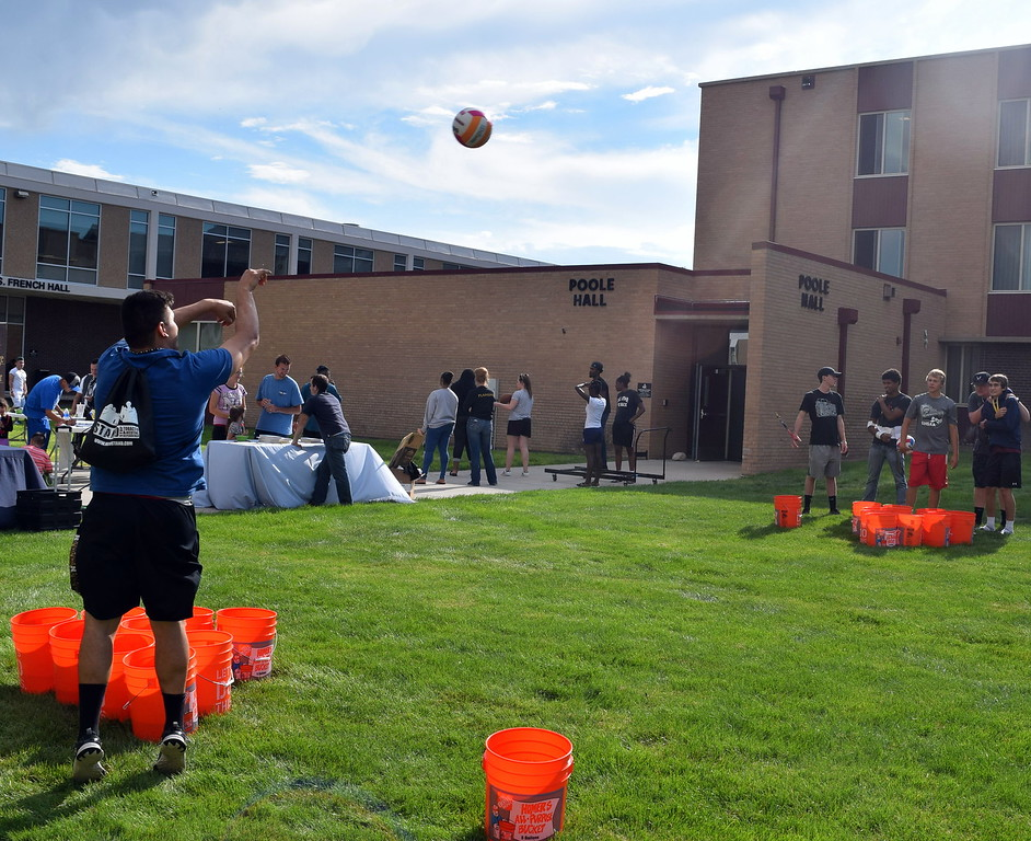 . Students try to toss volleyballs into a bucket Thursday, Aug. 17, 2017, at Northeastern Junior College\'s BBQ and Community Club Fair, part of the college\'s move-in day activities.