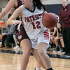 North Middlesex Regional High School girls basketball played Groton Dunstable Regional High School on Saturday in Townsend. GD's #10 Rachel Erickson covers NM's #12 Lexi DeSimone as she drives to the basket. SENTINEL & ENTERPRISE/JOHN LOVE