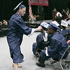 North Middlesex Regional High School graduation was held on Friday night at Fitchburg State University Recreation Center. Graduate Akia Gonkar, seated, high fives his classmate Josh Straitiff during the ceremony. SENTINEL & ENTERPRISE/JOHN LOVE