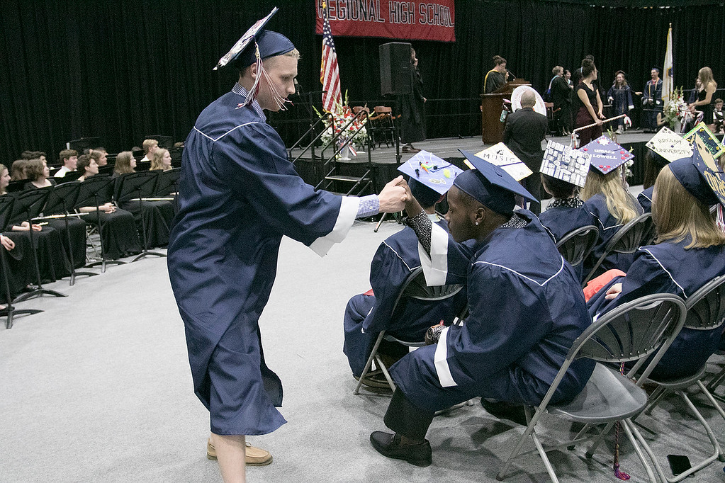 . North Middlesex Regional High School graduation was held on Friday night at Fitchburg State University Recreation Center. Graduate Akia Gonkar, seated, high fives his classmate Josh Straitiff during the ceremony. SENTINEL & ENTERPRISE/JOHN LOVE