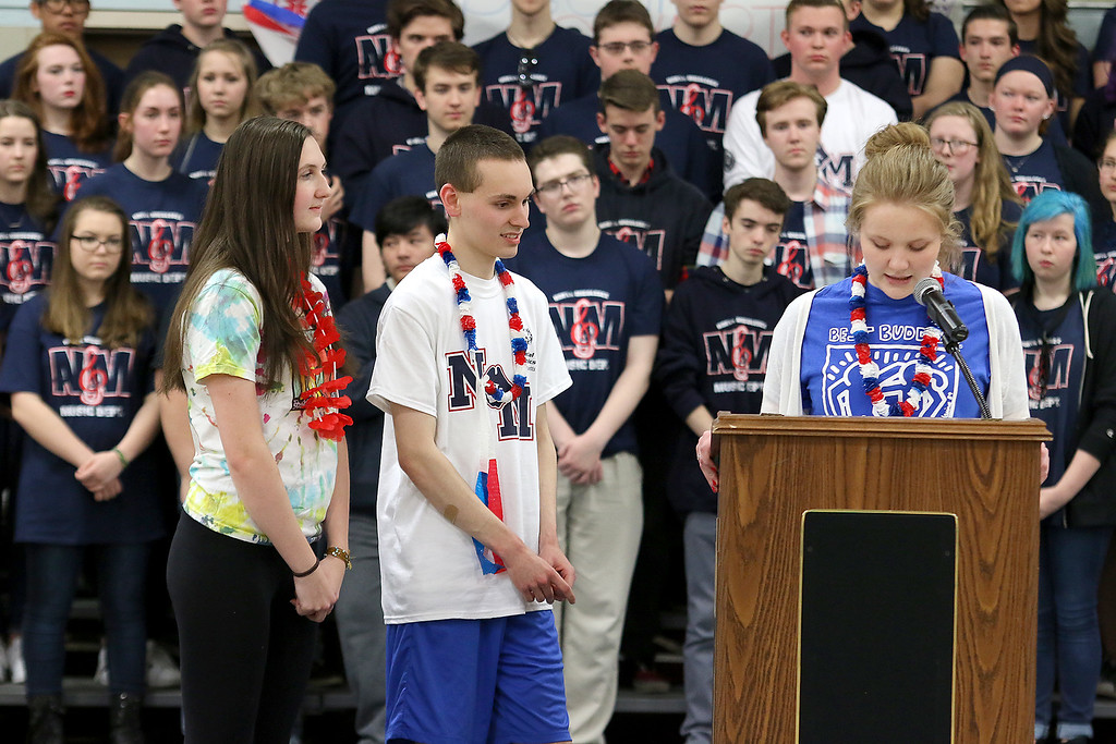 . North Middlesex Regional High School seniors, from left, Sarah Stadeler, Alec Guth and Clancy Ronan, at microphone, tell the history of the Special Olympics at the 10th annual pep rally for the schools athletes that will be participating in Friday\'s Special Olympics at Fitchburg State University. SENTINEL & ENTERPRISE/JOHN LOVE