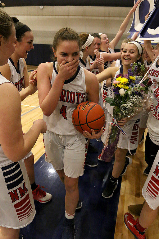 . North Middlesex Regional High School player Hadley Beauregard after making two points in the start of the game was crowded around by her team. She had already reached 1000 points but after this basket, in front of her home crowd, she was honored for making that mile stone. SENTINEL & ENTERPRISE/JOHN LOVE