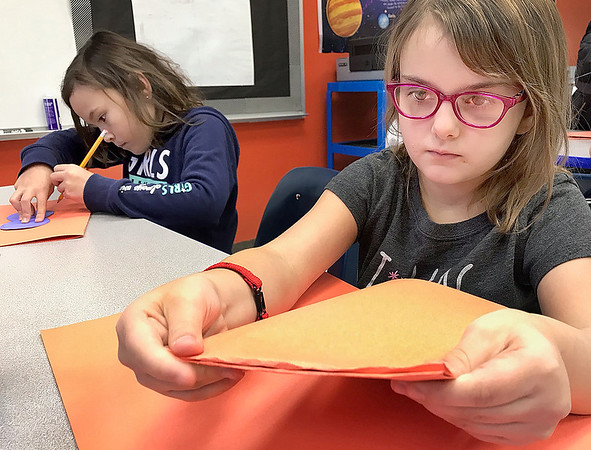 KEVIN HARVISON | Staff photo<br /> Alexis Conley, right, cuts out her paper for a pumpkin decoration in her Emerson STEAM class along with Temperance Harris, left.