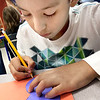 KEVIN HARVISON | Staff photo <br /> Salvador Garcia traces a templet to make a Fall decoration Friday at Emerson Elementary School.
