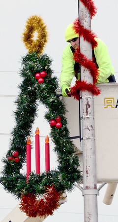 KEVIN HARVISON | Staff photo<br /> McAlester city employee trys to stay warm as he secures a Christmas decoration and wraps a light pole on Carl Albert Parkway with garland.