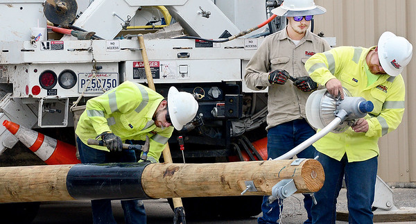 KEVIN HARVISON | Staff photo<br /> Linetec Services employees work to get a new street light up on Wyandotte Avenue near Main Street Tuesday.