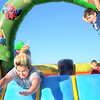 KEVIN HARVISON | Staff photo <br /> Brileigh Treannie, left, leaps head first while playing on an inflatable during the Kennedy Eye Care Fall Festival Thursday.