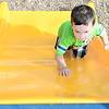 Kevin Harvison | Staff photo<br /> Washington Early Childhood / Kibios Head Start Center student Eli Free attempts to make it back to the top of the playground slide.