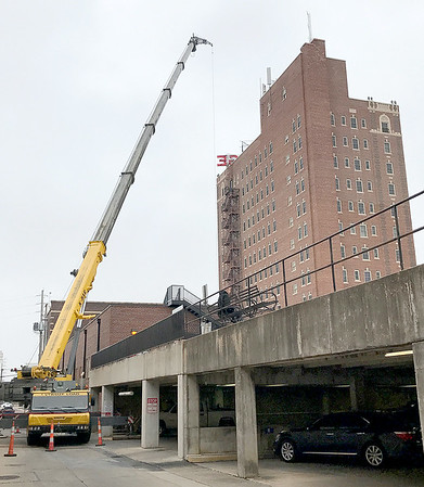 Kevin Harvison | Staff photo<br /> A large crane works from the alley between the First National Bank and the Aldridge Monday morning.