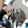 Kevin Harvison | Staff photo<br /> Former McAlester Buffolo graduate Evan Smith paints a mural on the backside of a business between Third Street and Fifth Street.