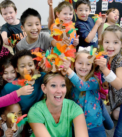 Kevin Harvison | Staff photo<br /> A flock of turkeys hover above the head of Emerson Elementary first grade teacher Mindi Harvison after making the birds during a class project.