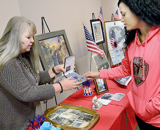 Kevin Harvison | Staff photo<br /> McAlester Kiamichi Technology Center Health Careers Certifications instructor Marilyn Turvey, LPN, left, shows off a Purple Hart Medal from her familys exhibit in the KTC War Museum to Tori Stowers, KTC Medical Assisting student. The museum will be open to the public through Thursday 16th.