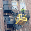 Kevin Harvison | Staff photo<br /> Workers work from the end of a  large crane works from the alley between the First National Bank and the Aldridge Monday morning.