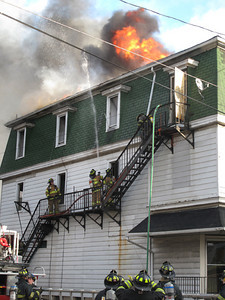 Flames shoot through the roof of an apartment building at the intersection of North Lehigh Avenue and Spring Street in Frackville Saturday afternoon.