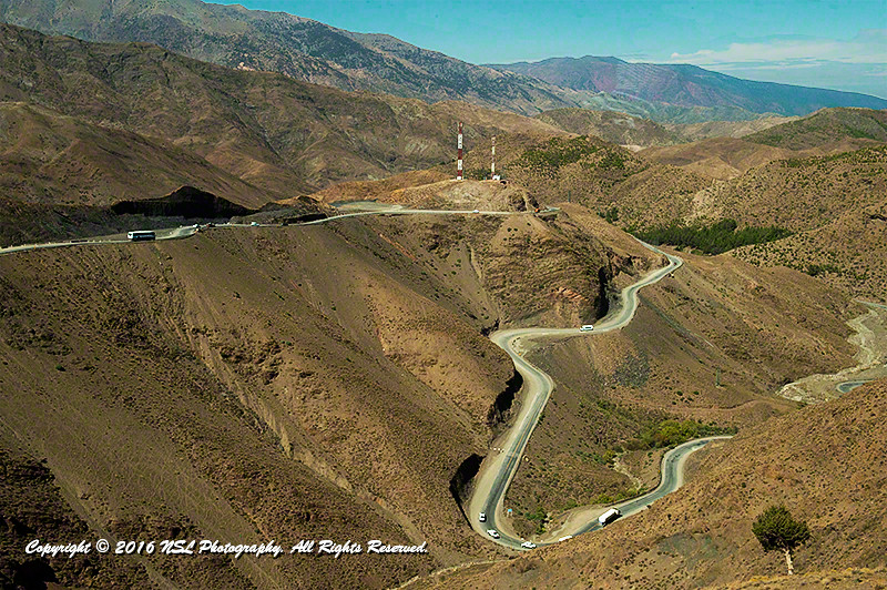 At the road's edge, driving on the hairpin turns through the High Atlas Mountains, to Marrakech.
