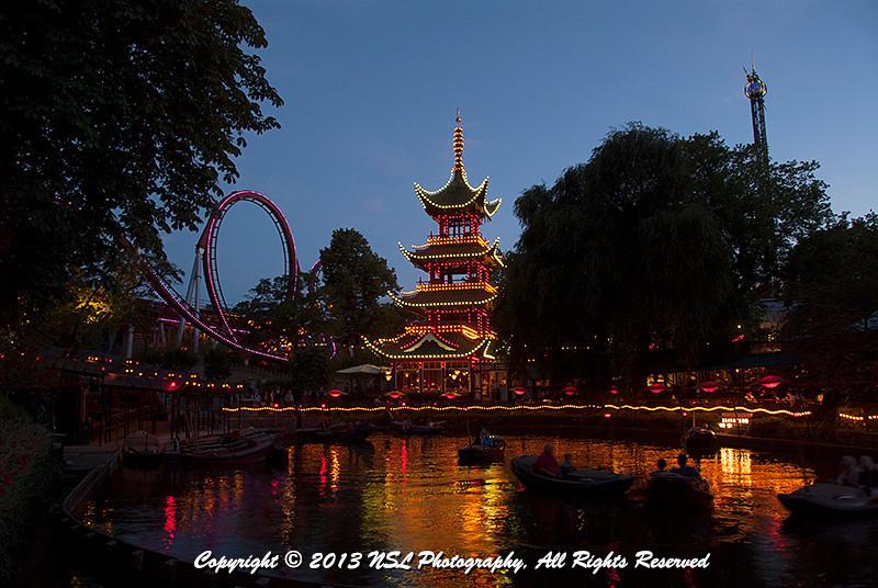 Dæmonen (The Demon) roller coaster on the left, in the Danish amusement park, Tivoli Gardens, Copenhagen, Denmark at dusk