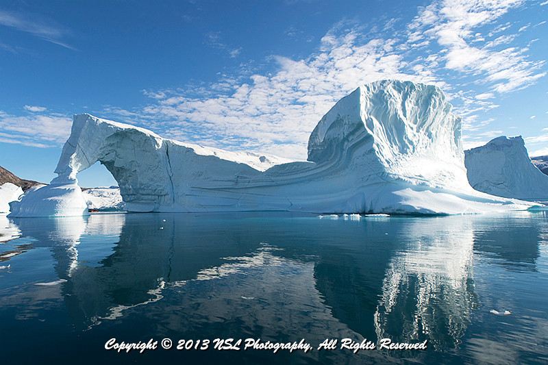 Iceberg Graveyard in Rodefjord, Scoresby Sund, Greenland - Zodiac peeking out under the arch