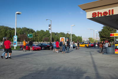 Owners and passengers gather around the Shell Station