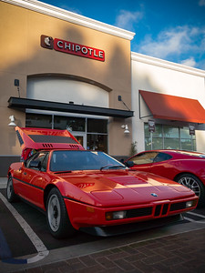 A spicy orange BMW M1 parks in front of Chipotle