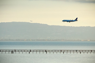 As this aircraft lands at SFO, another takes flight from Oakland International Airport