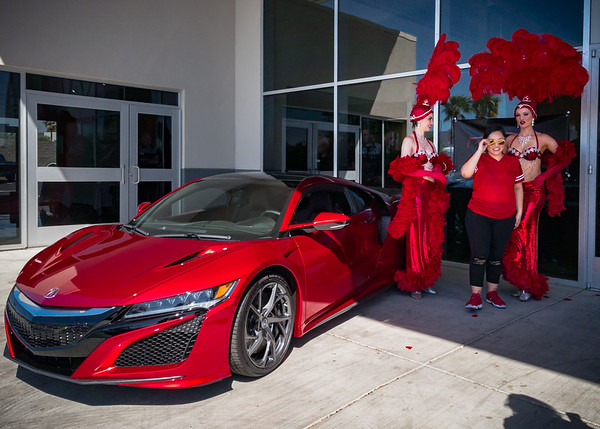 The dealership has a red 2017 NSX parked in front with a pair of showgirls wearing appropriate color-matched attire.  Unfortunately the morning sun casts a harsh shadow across the car...so I am not exactly eager to take photographs of owners posing with them.