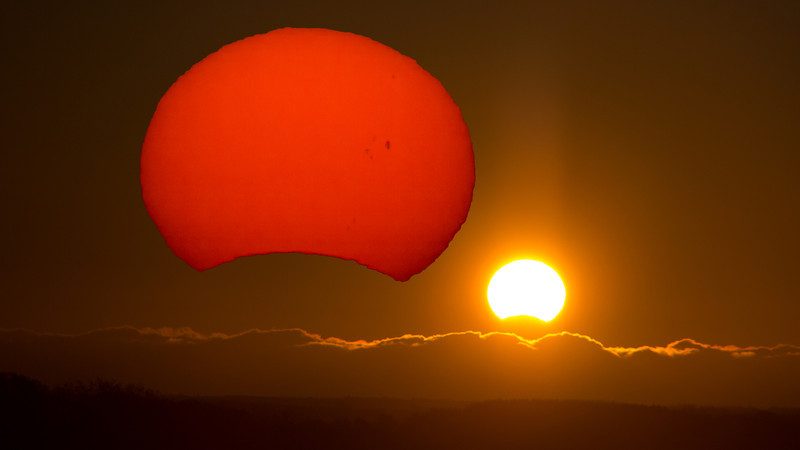 """Andreas Gada, This is a composite photograph of the partial annular eclipse that was visible at sunrise on November 3, 2012.  The images were taken from my backyard on Sandy Flats road near Roseneath Ontario.  The first image was taken with a Canon 60D camera using a 200 mm lens, f/8, 1/8000"""" exposure and ISO 100.  This image shows the relationship of the sun relative to the ground and the bank of clouds on the horizon.  Superimposed on this image is a close-up view of the sun showing surface details.  It was taken through an 130mm f/6 telescope (800mm focal length) using a Canon 60Da, ISO 100, 1/1250"""" exposure and a Thousand Oaks ND4 filter."""