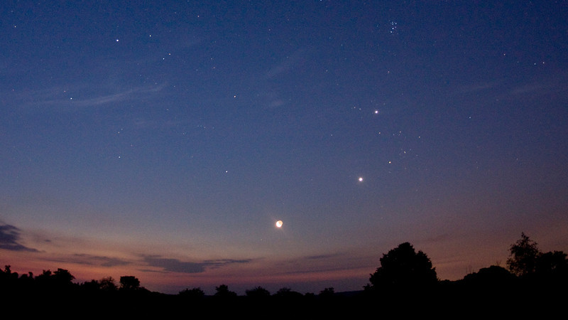 "Andreas Gada, Moon Jupiter and Venus conjunction July 16, 2012 4:17 EDT as seen from Sandy Flats near Roseneath ON.  Canon Rebel XSI, Nikon 16 mm f/3.5, ISO 1600 with a 15"" exposure."