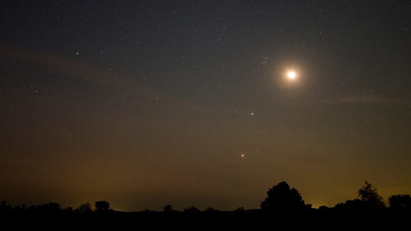 "Andreas Gada, Moon Jupiter and Venus conjunction July 14, 2012 3:59 EDT as seen from Sandy Flats .  Canon 20Da, Canon 10 – 22 mm lens set at 15 mm and f/4.5, ISO 1600 with a 20"" exposure."