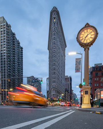 Flatiron Building, Tiffany Clock, and a speeding taxi early in the morning.