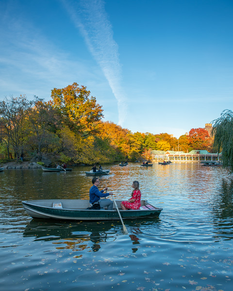 Central Park with boaters in the foreground and Loeb boat house in the background.  Fall colors.