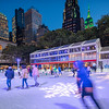 Skaters in Bryant Park with the Empire State Building in green in the background.