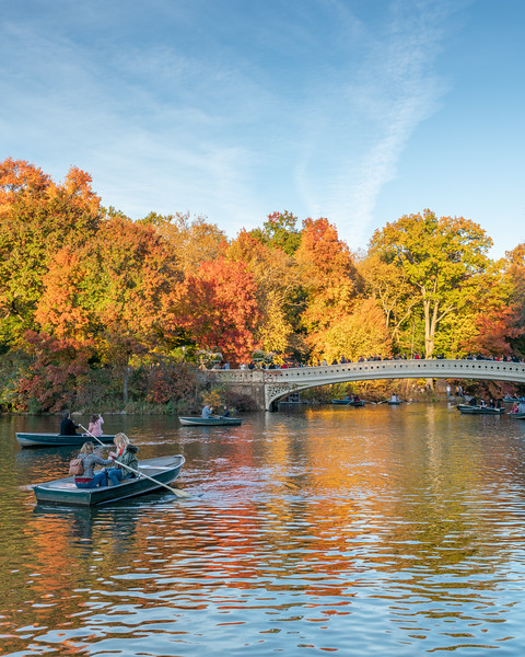 Boaters near the famous Bow Bridge in Central Park during the fall.