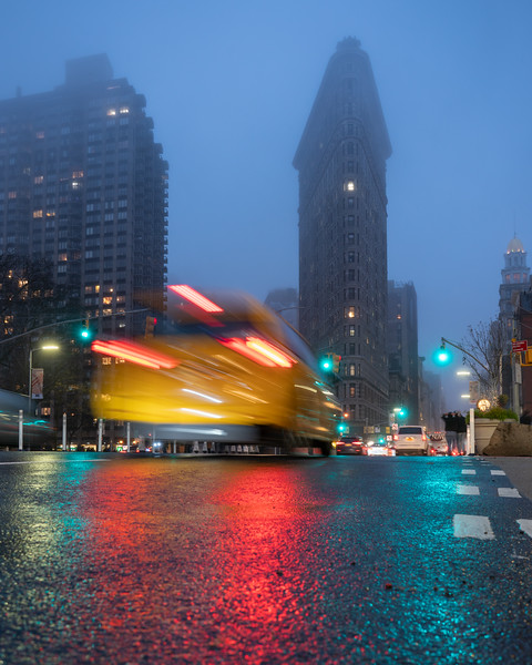 Flatiron Building in fog after the rain with a speeding taxi.