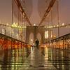 Couple sharing an umbrella in the rain on the Brooklyn Bridge.