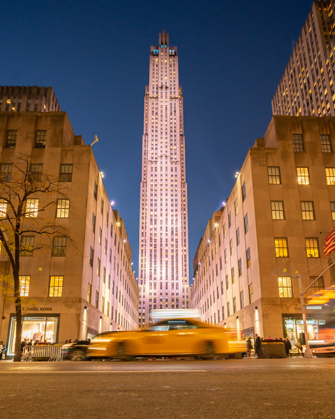 Rockefeller Center and speeding taxi during the blue hour.