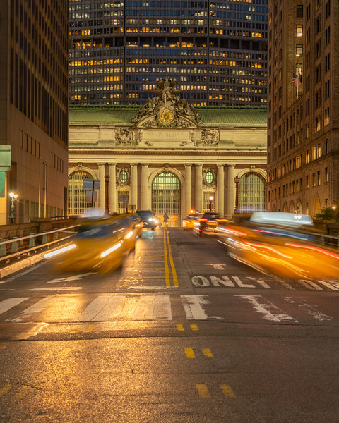 Blurred taxis on Park Avenue with Grand Central and the Met Life Building in the background during the blue hour.