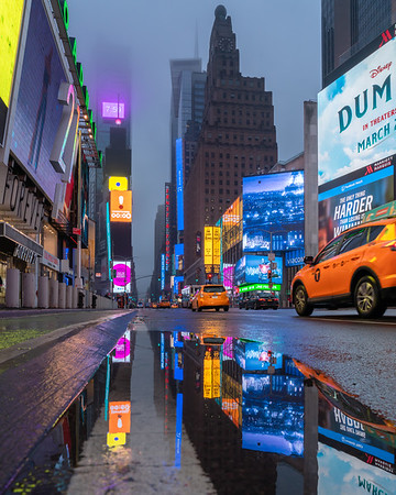 Times Square in the rain with passing taxis and reflections in a puddle.