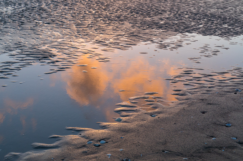 Reflected clouds at Orewa beach